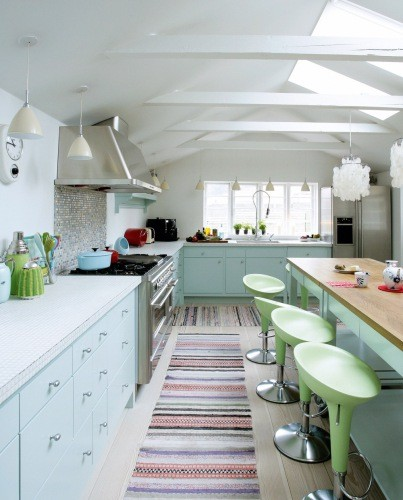 a pastel kitchen with powder cabinets, green stools, stainless steel appliances and striped rugs is cheerful and cool