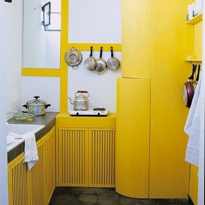 a lemon yellow kitchen with large white tiles and a concrete floor has a fresh feel and a very bold look