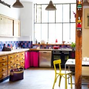 a loft kitchen with vintage cabinets, a colorful tile backsplasj, bold touches and textiles is cool and bright