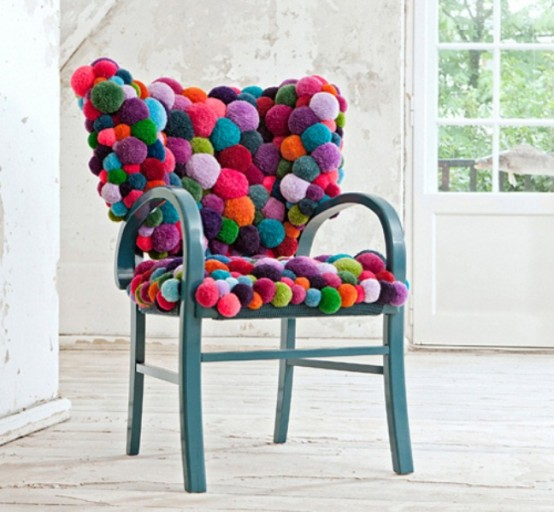 a blue chair fully covered with colorful pompoms is a gorgeous piece to sit on - it's cozy, warm and bright