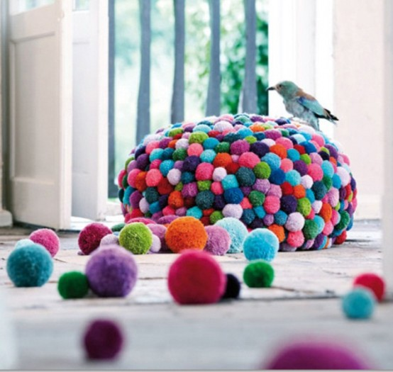 a colorful pompom pouf will accent your space and make it cheerful, you can DIY this piece easily