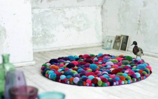 a colorful round pompom rug is a bright accessory that you may enjoy and with which you may accent your space