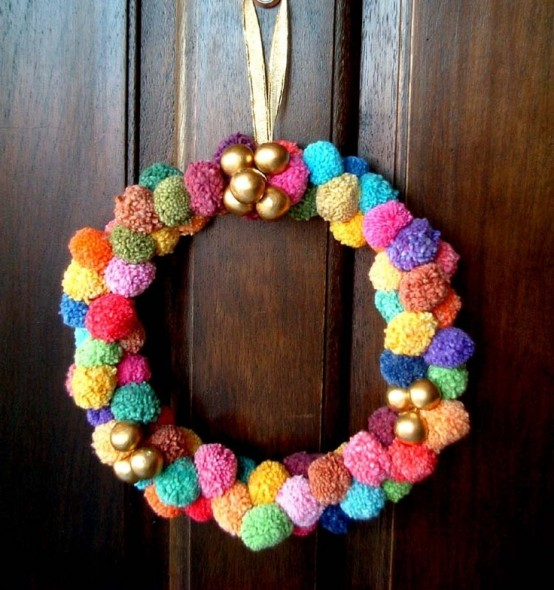 a colorful pompom wreath with gold ornnaments is a nice idea for Christmas or New Year and it will bring much color
