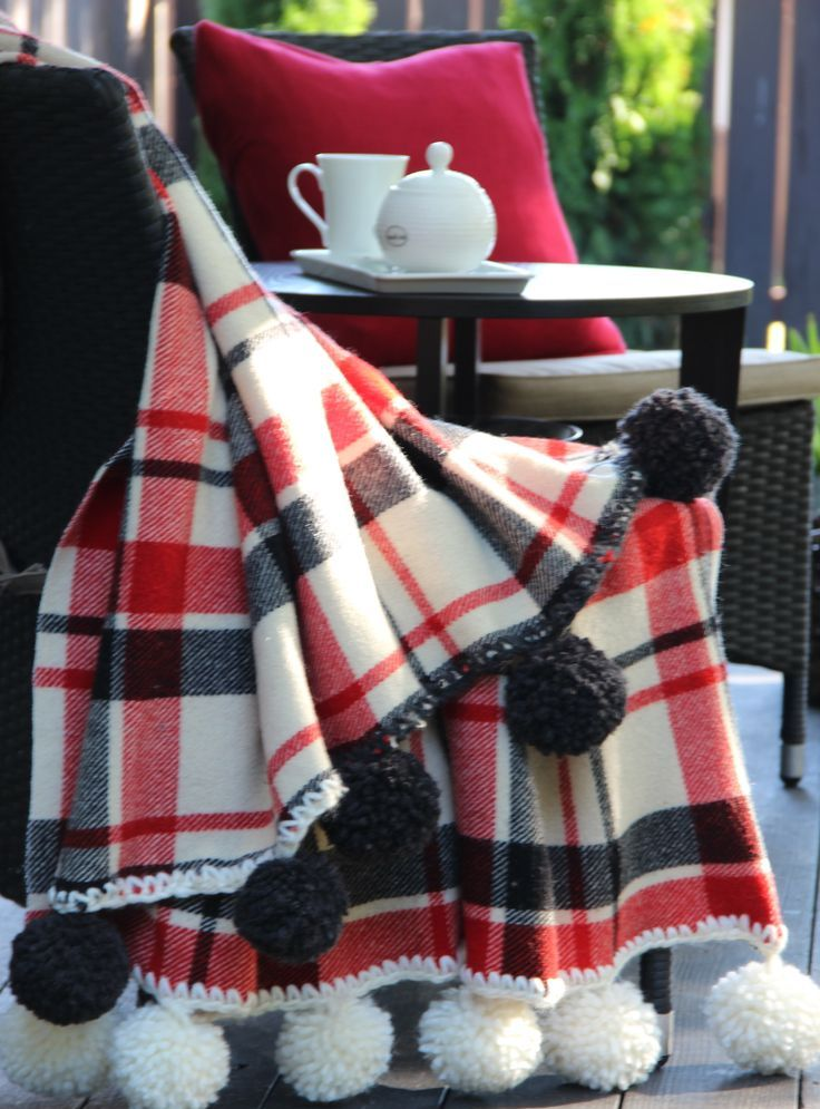 a plaid blanket accented with oversized pompoms is a cozy and cool piece to cover up on cold days