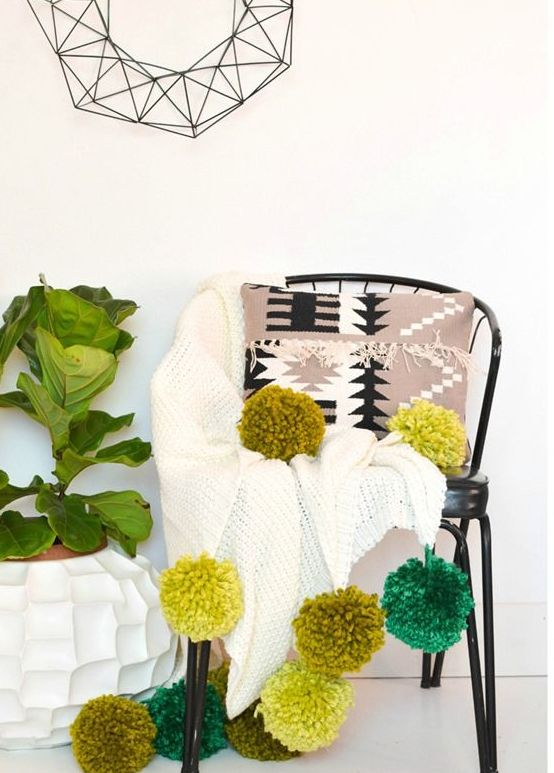 a white crochet blanket with oversized mustard and green pompoms that add color and fun to the piece