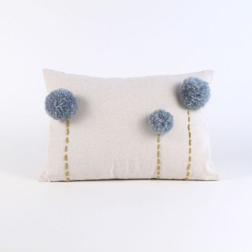 a neutral pillow with grey pompoms that accent it and imitate blooms is a cool and whimsy decoration for your space