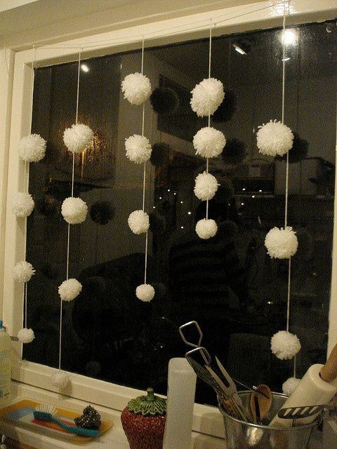 white pompom garlands like these ones will make your windows look veyr wintry-like and very cozy