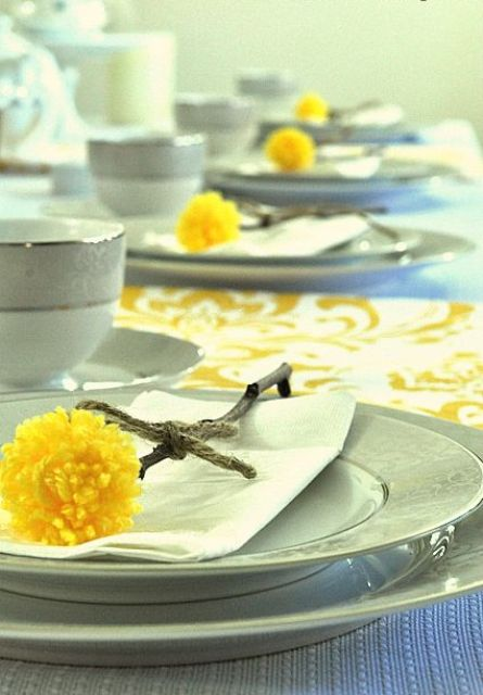billy balls made of sticks and yellow pompoms are a nice way to accent place settings for spring