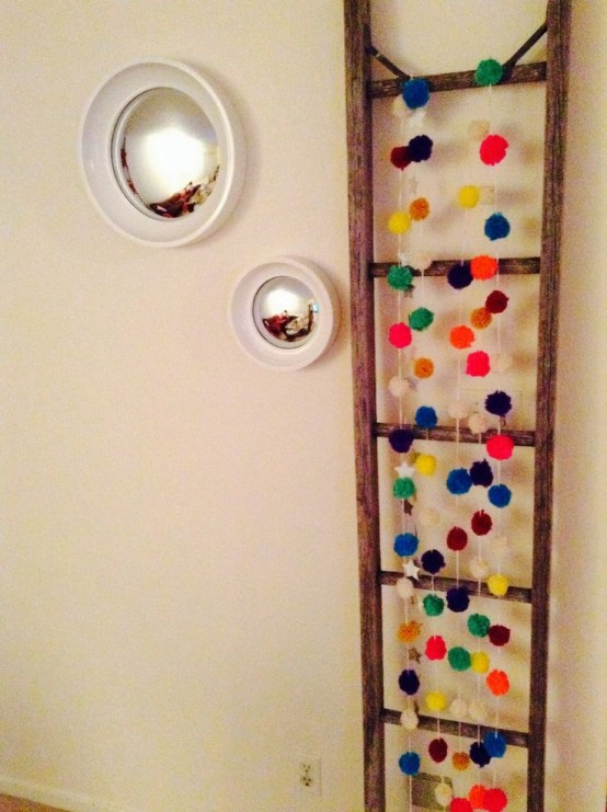 hang some colorful pompoms on a ladder to make your space more bright and fun without much effort