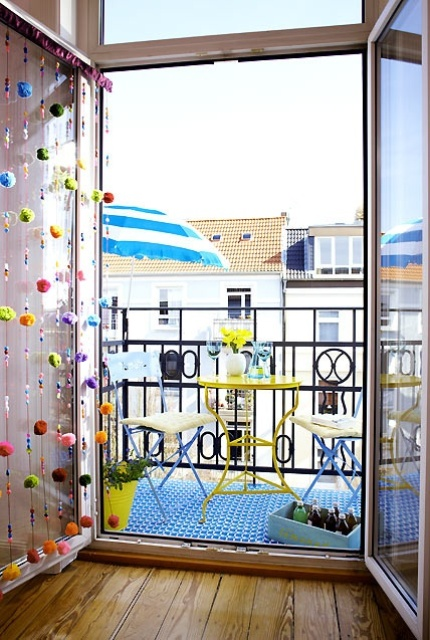 a balcony door accented with colorful pompoms and beads is a stylish idea for a modern and cheerful space