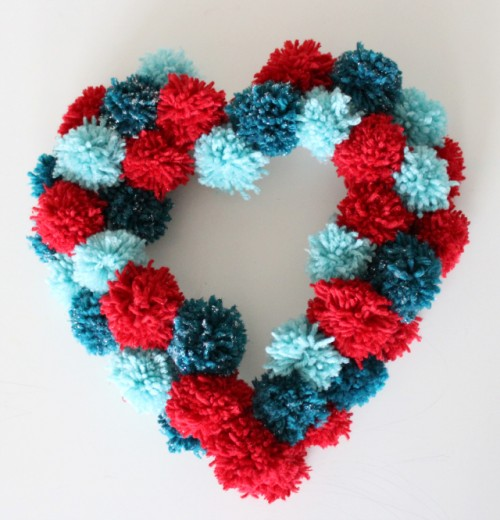 a colorful pompom heart-shaped wreath is a nice decoration for Valentine's Day or just for romantic decor