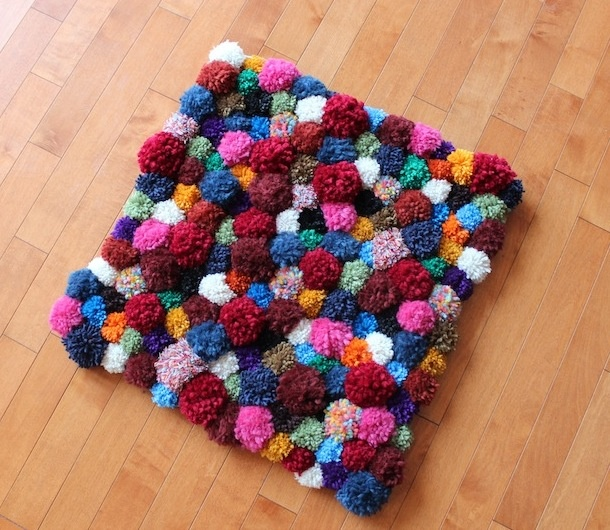 a colorful pompom mat can be a nice idea not only for a bathroom but also for any other space, add more color to the interior