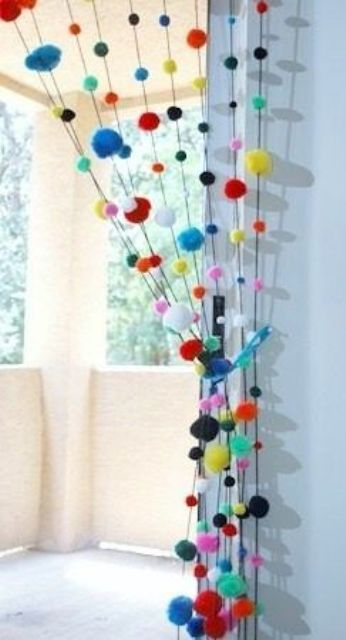 colorful pompom curtains to divide the balcony from the rest of the interior - it's an easy way to do that and you can DIY that
