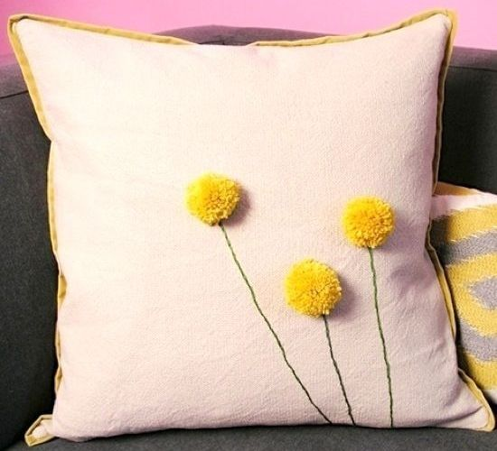 a neutral pillow with gold edges with yellow pompoms that imitate billy balls is a nice accessory for spring