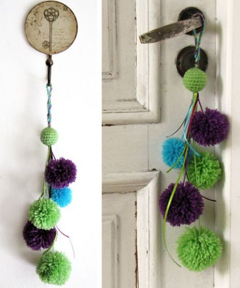 a colorful green, blue and purple pompom hanging can accent a door or some other item or space and add color to it