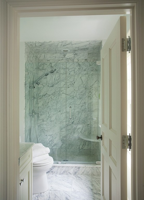 a laconic white marble bathroom with a shower space and a vanity - you won't need more than that