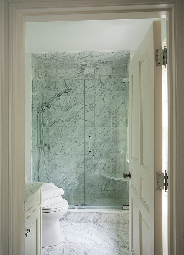 a laconic white marble bathroom with a shower space and a vanity   you won't need more than that
