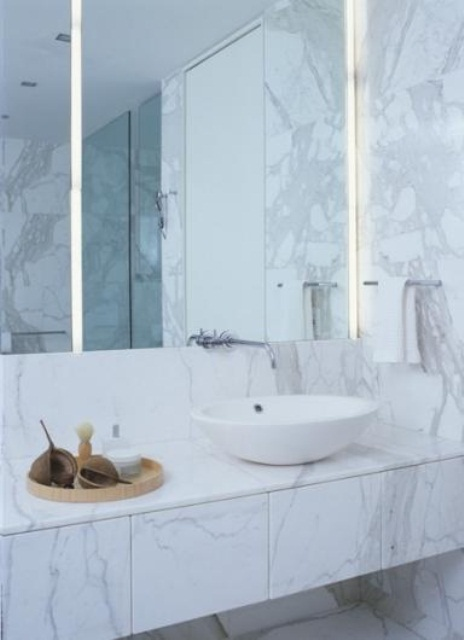a minimalist bathroom done with white marble tiles and large lit up mirrors plus a vessel sink is chic