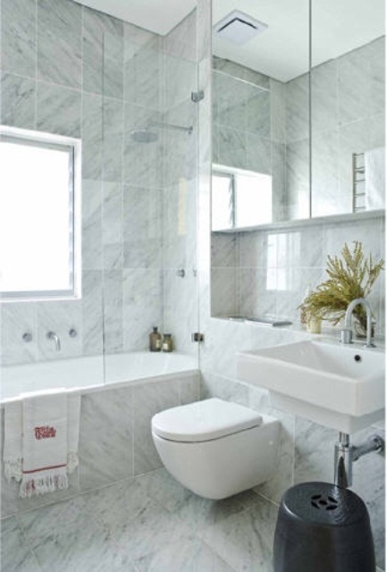 a neutral contemporary bathroom clad with marble tiles, with a tub, a toilet and a large mirror cabinet on the wall