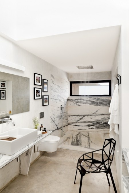 a neutral bathroom done with a concrete floor, white and black marble in the shower space and a black geometric chair