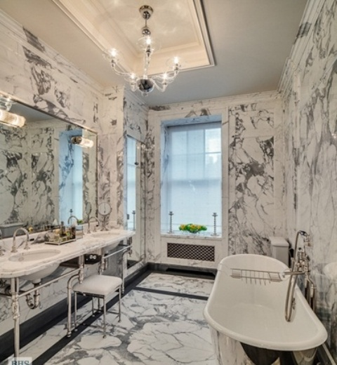 a luxurious vintage-inspired bathroom clad with white marble completely, with a metallic tub and sinks on stands