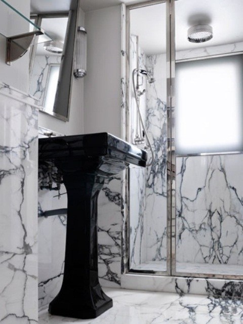 a tiny yet luxurious bathroom done with white and black marble, with a shower space and a black free-standing sink