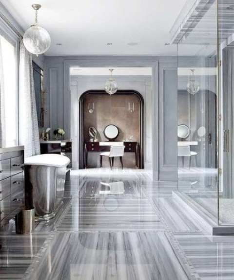 a vintagegrey bathroom with a grey marble floor, a shower space, a metallic tub and a vanity next to one wall