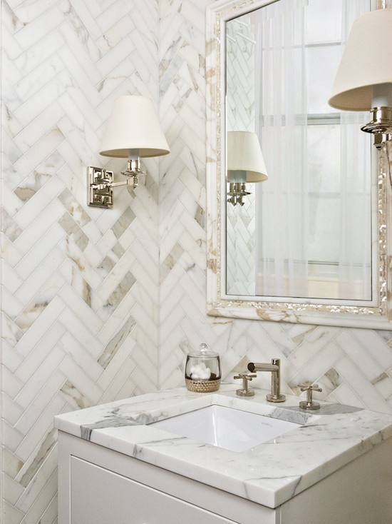 a small yet luxurious marble powder room with chevron clad walls and a chic mirror plus wall lamps