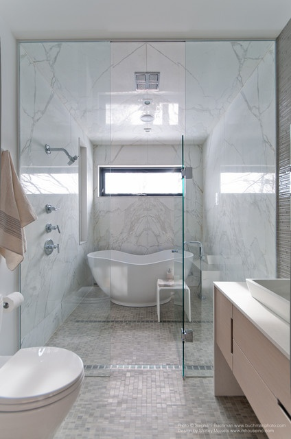 a marble bathroom with a shower space done with marble and tiles, a sleek vanity, seamless glass shower doors