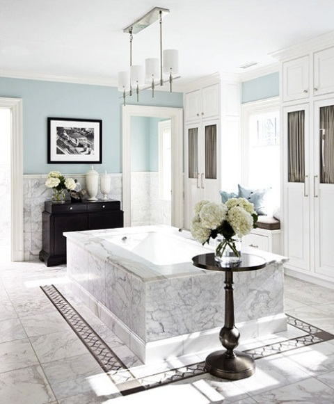 an elegant white marble and light blue bathroom with a marble clad tub and dark touches for a more dramatic look