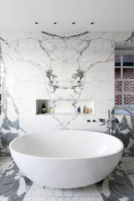 a bright contemporary bathroom done with white and grey tiles, amodern oval tub and windows