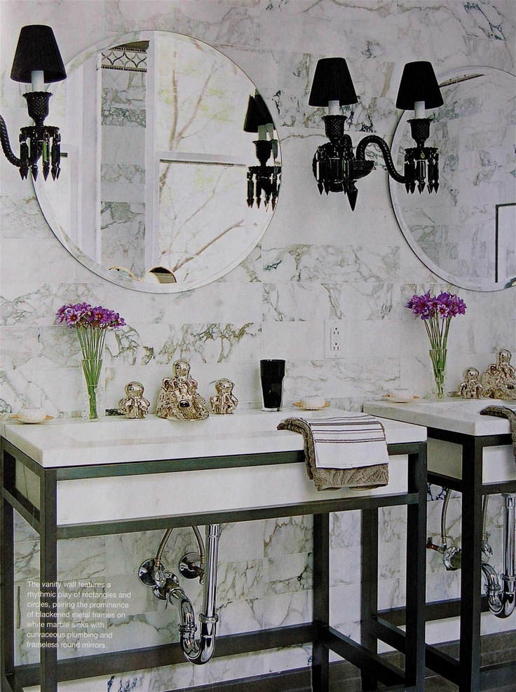 a luxurious white marble bathroom with sinks on stands, elegant black lamps and round mirrors