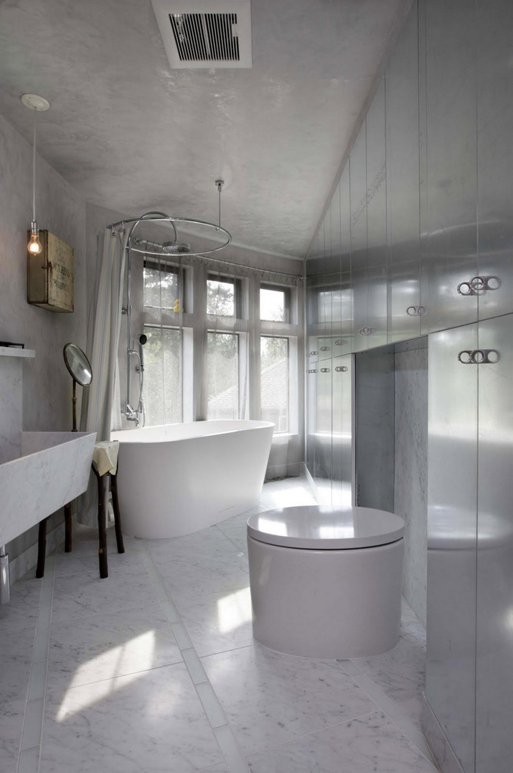 an unusual white marble bathroom done with metal panels, an oval tub and a sculptural sink of marble