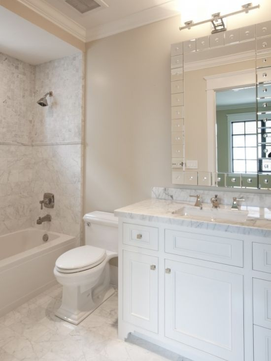 a chic neutral bathroom with marble tiles on the floor and in the tub space, a marble clad vanity and a stylish mirror