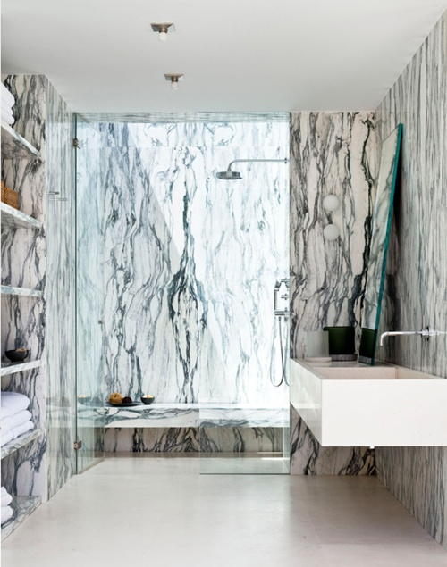 a statement contemporary bathroom all done with white and black marble on the walls, in the shower space and with marble shelves