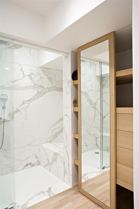 a minimalist bathroom done with white marble in the shower zone and a large sleek closet of wood to store everything