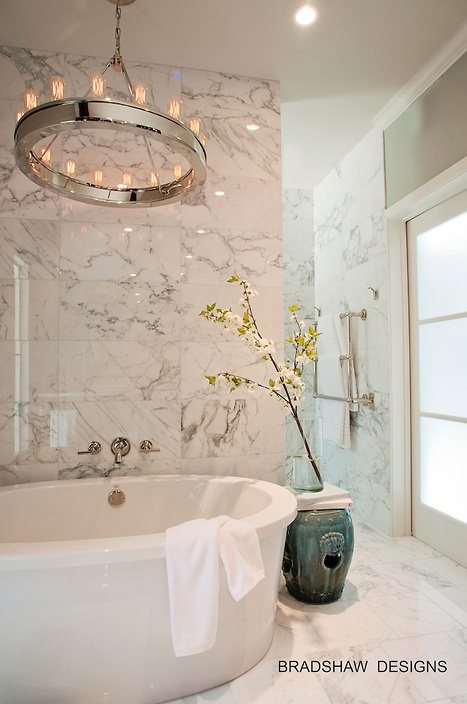 a luxurious modern bathroom clad with white marble, with a round tub, a statement chandelier and a frosted glass window