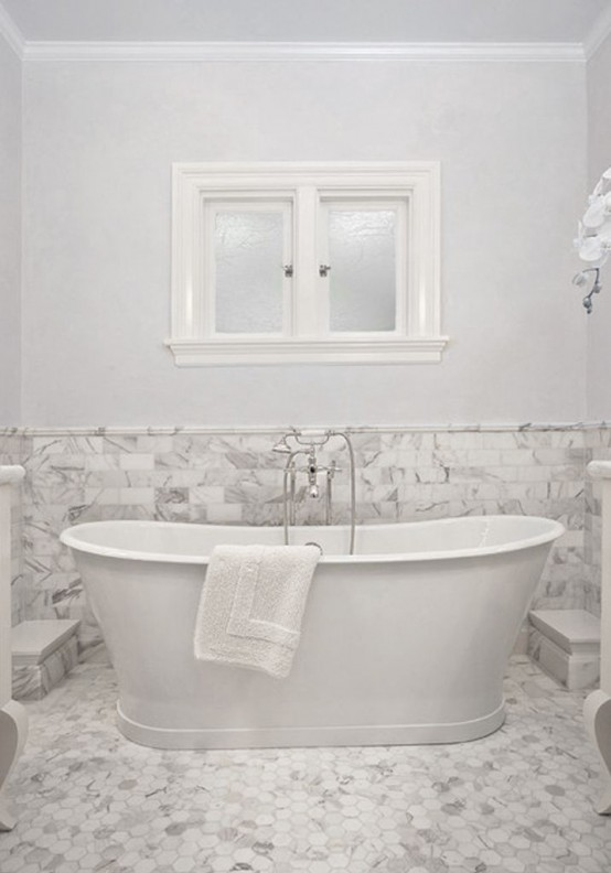 a vintage bathroom done in white and with white marble tiles on the walls and floor plus an oval tub