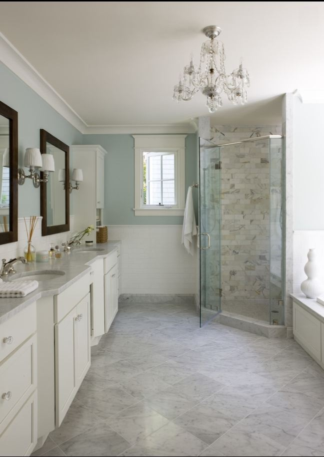 a modern farmhouse bathroom with aqua walls, neutral vanities, a shower space with marble tiles and floor