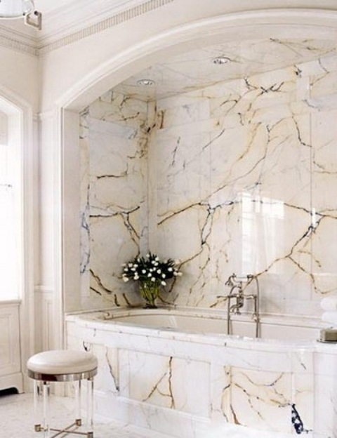 a chic and refined bathroom with a tub space all clad with catchy marble panels