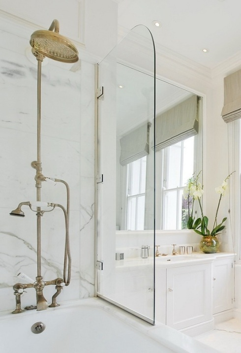 an elegant bathroom done in creamy, with vintage hardware and white marble in the tub zone
