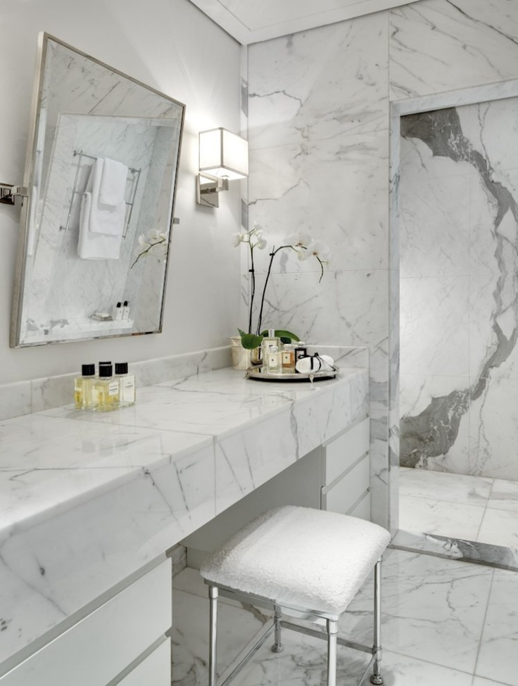 a contemproary luxurious bathroom done with white marble everywhere, with a sleek vanity and a large mirror