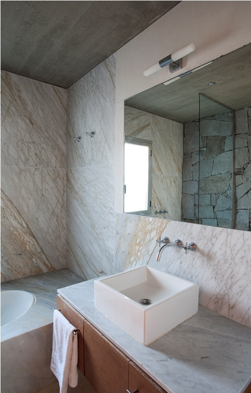 a unique bathroom pairign marble and stone, with a floating vanity and a square sink plus a mirror