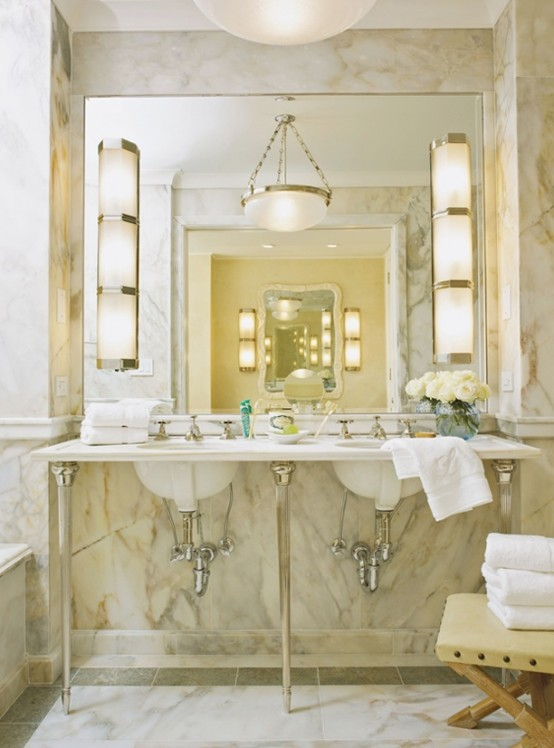 an elegant and chic warm-colored marble bathroom with many lamps, a sink on a stand and a large mirror