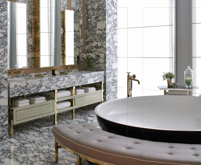 a unique bathroom with a round tub, a pink curved bench, a built in vanity and much black and white marble