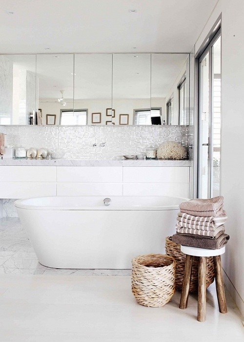 an eclectic bathroom featuring an oval tub, marble tiles and shiny ones on the wall, a floating vanity and mirror cabinets