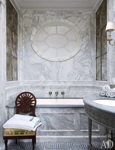 a gorgeous vintage grey marble bathroom with a tub, a sink on a stand and a round frosted glass window