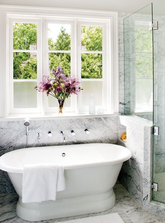 a chic and refined white marble bathroom with an oval vintage tub and a large window to enjoy the views