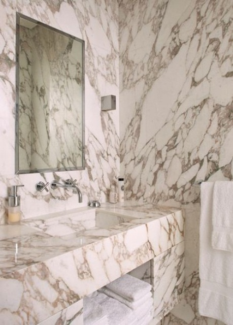 a chic white marble bathroom with marble covering and cladding everything plus a mirror