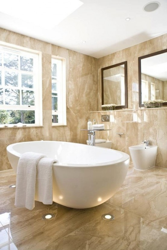 a beige bathroom fully clad with marble, with an oval tub, large mirrors and a window for more light